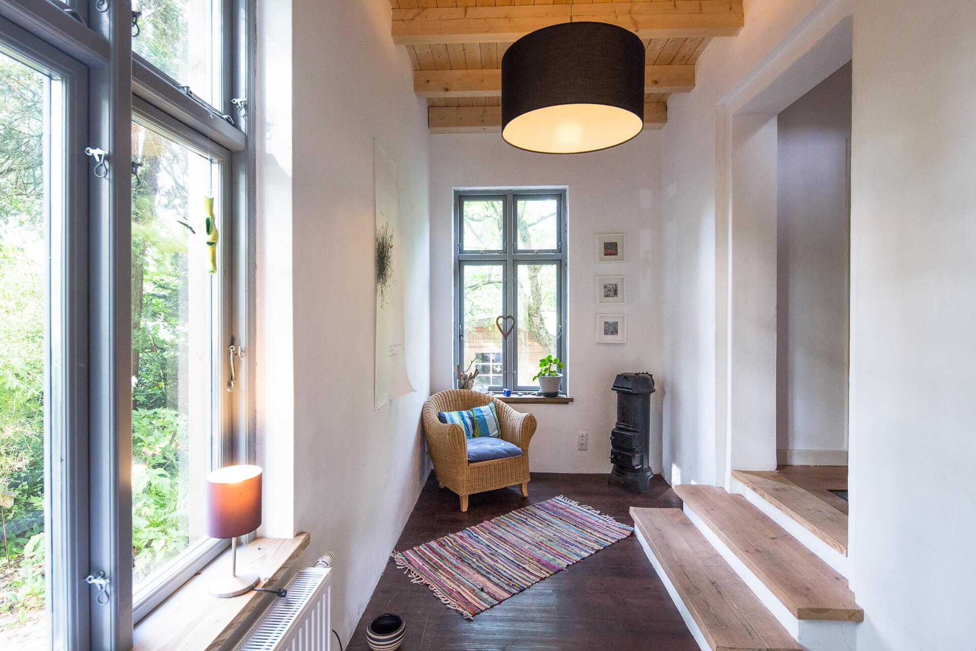Foto Ryan Baugestaltung Anbau Volksdorf Innenansicht zeigt Flur mit Sessel und Holzboden