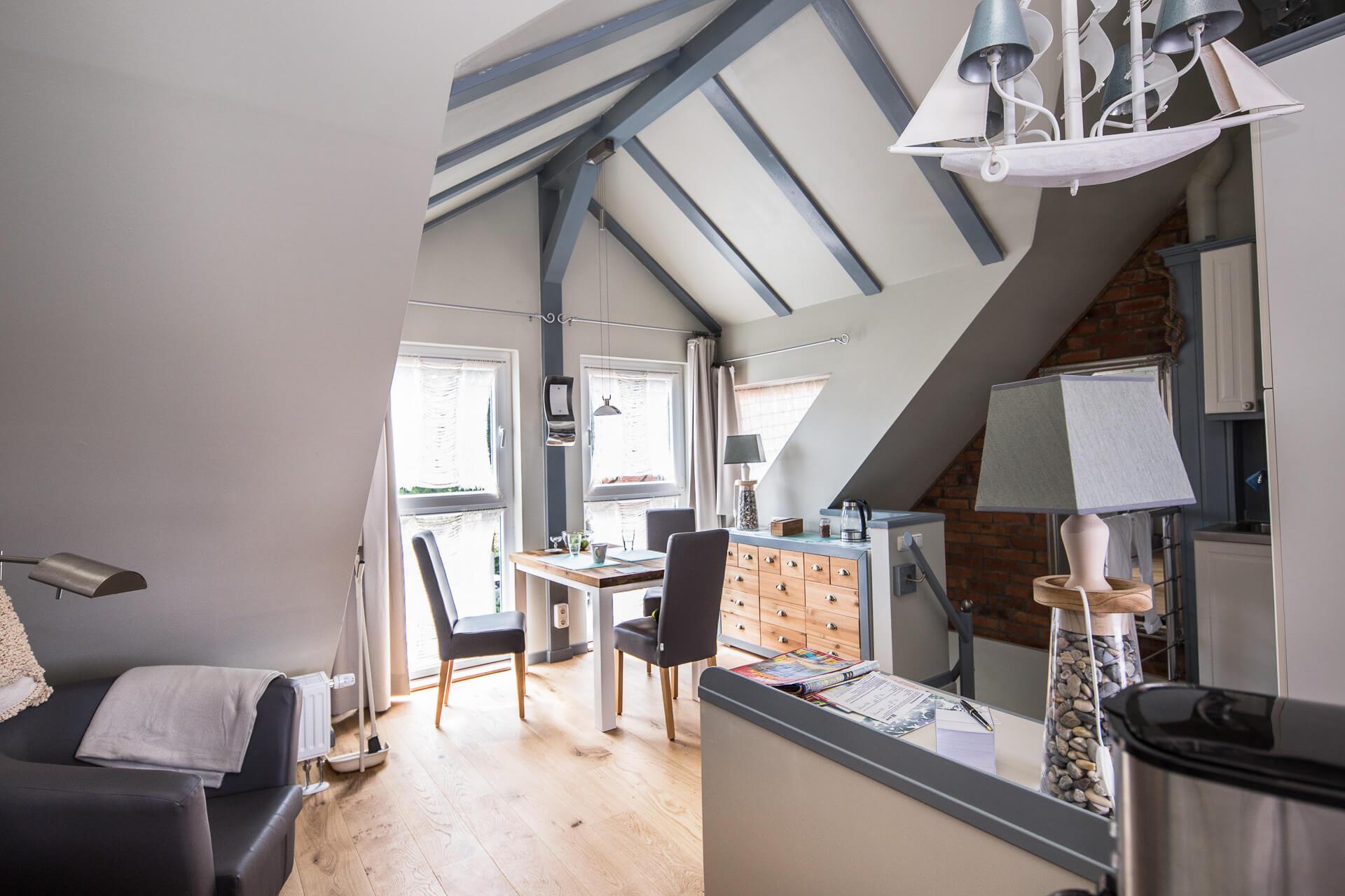 Foto Ryan Baugestaltung Appartmenthaus Lueneburg Wohnzimmer mit Holzgiebel, großen Fenstern und Sitzgelegenheit