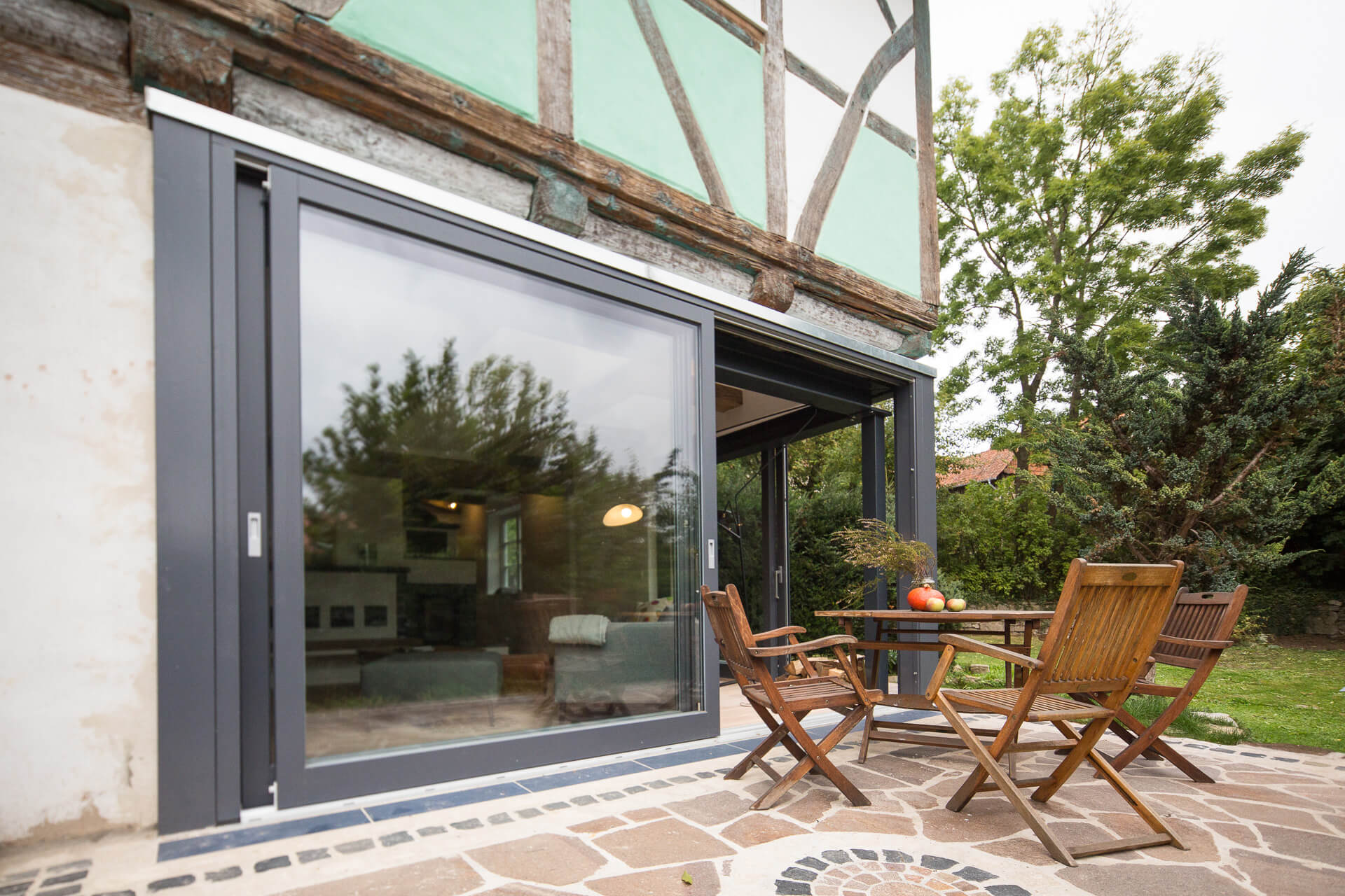 Foto Ryan Baugestaltung Fachwerkhaus Goettingen Terrasse mit Holzstuehlen und Tisch