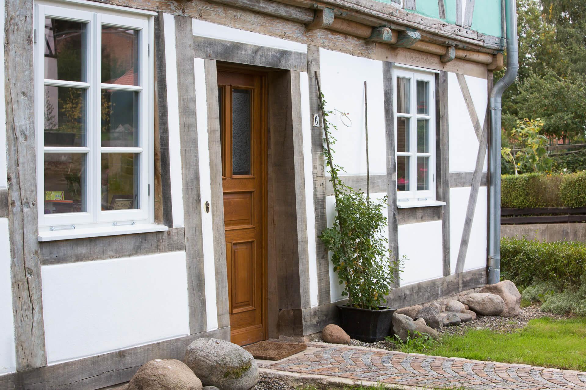 Foto Ryan Baugestaltung Fachwerkhaus Goettingen Eingangstür aus Holz und grüner Vorgarten