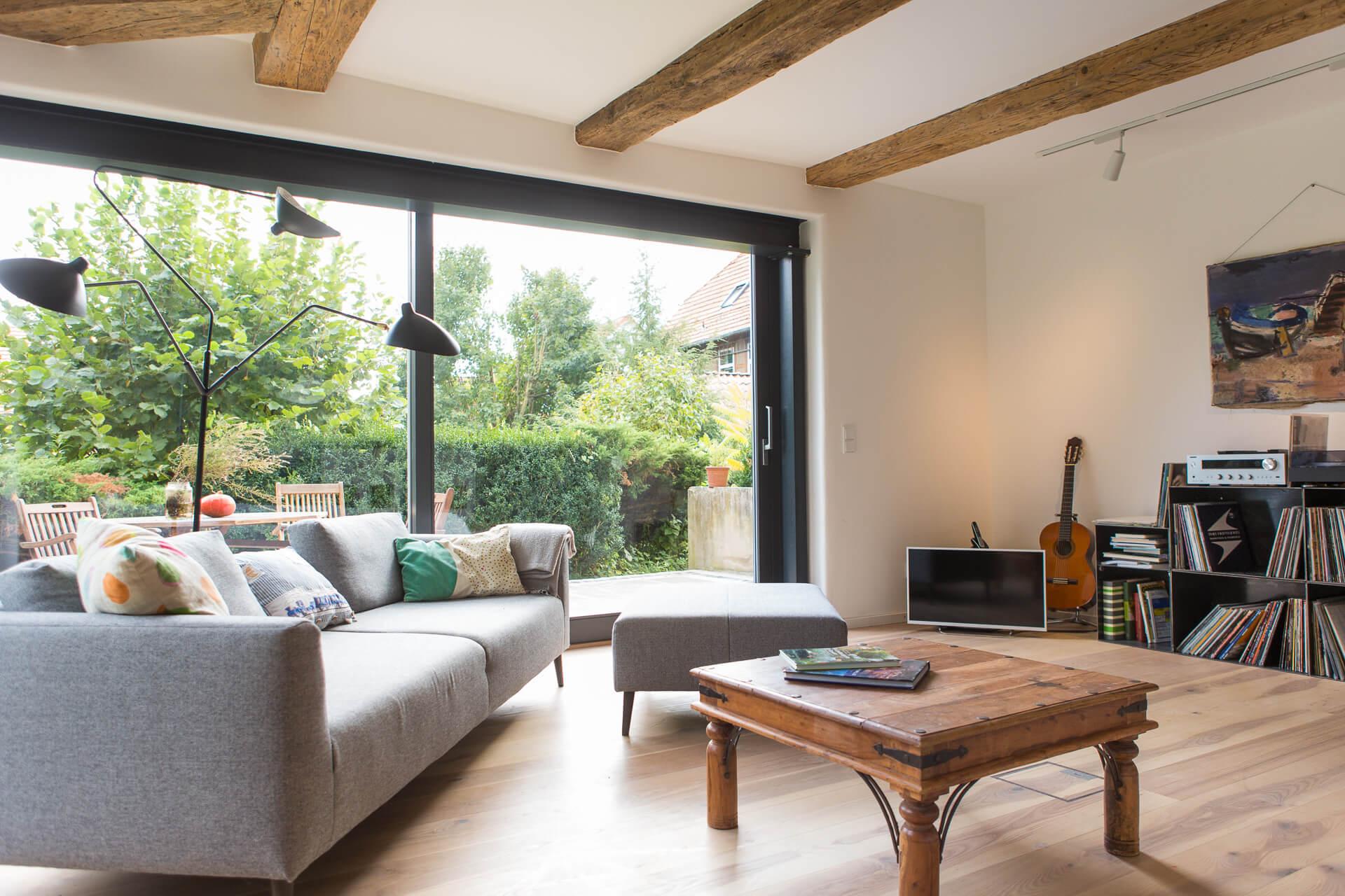 Foto Ryan Baugestaltung Fachwerkhaus Goettingen Wohnzimmer mit Couch und großen Terassenfenstern