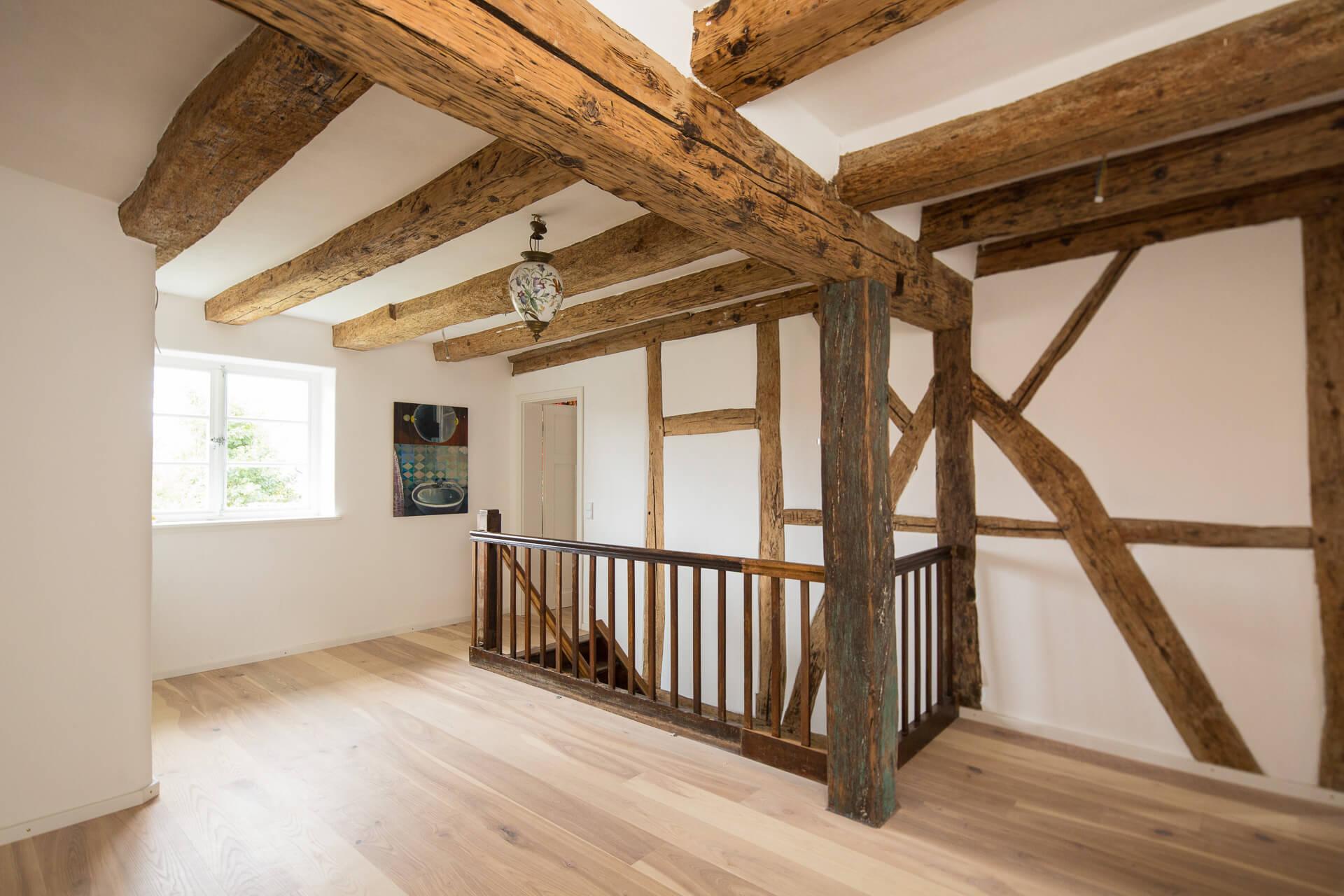 Foto Ryan Baugestaltung Fachwerkhaus Goettingen Raum mit Holzbalken und offener Holtreppe